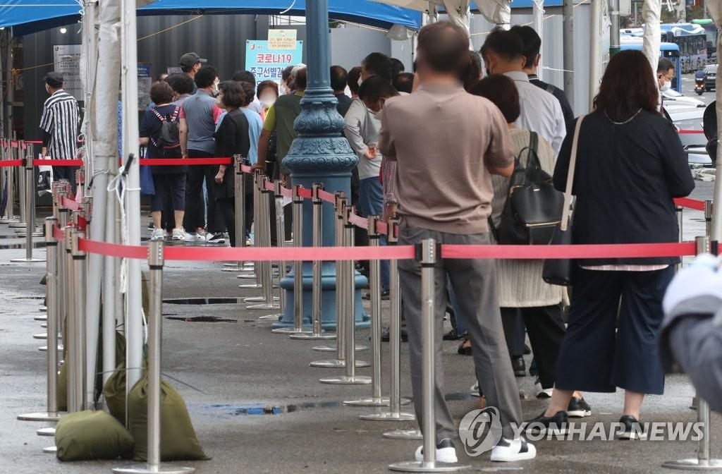 資料圖片:9月8日,在設于首爾站的篩查診所,市民們排長龍等待接受病毒檢測。 韓聯社
