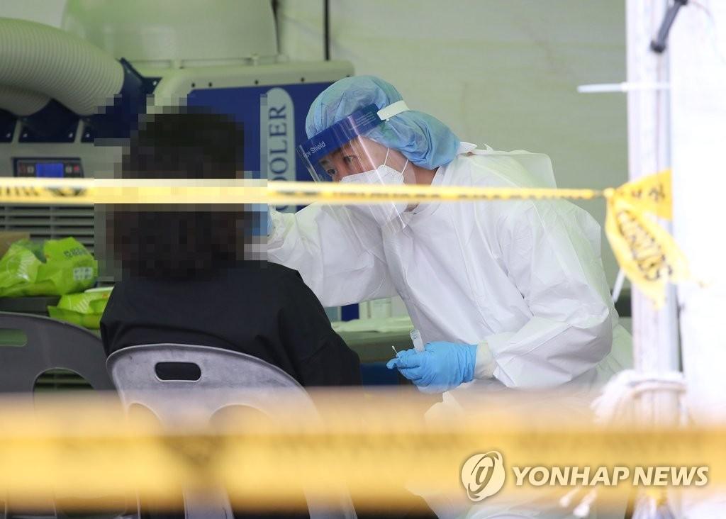 資料圖片:9月10日,在設于蔚山市中區綜合體育場的核酸檢測點,市民接受新冠病毒檢測。 韓聯社