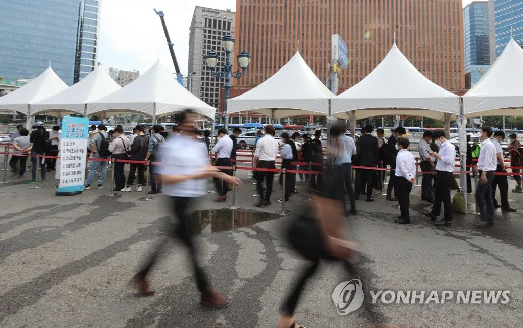 資料圖片:9月13日,在首爾火車站廣場的臨時篩查診所前,人們排隊等待檢測新冠病毒。 韓聯社