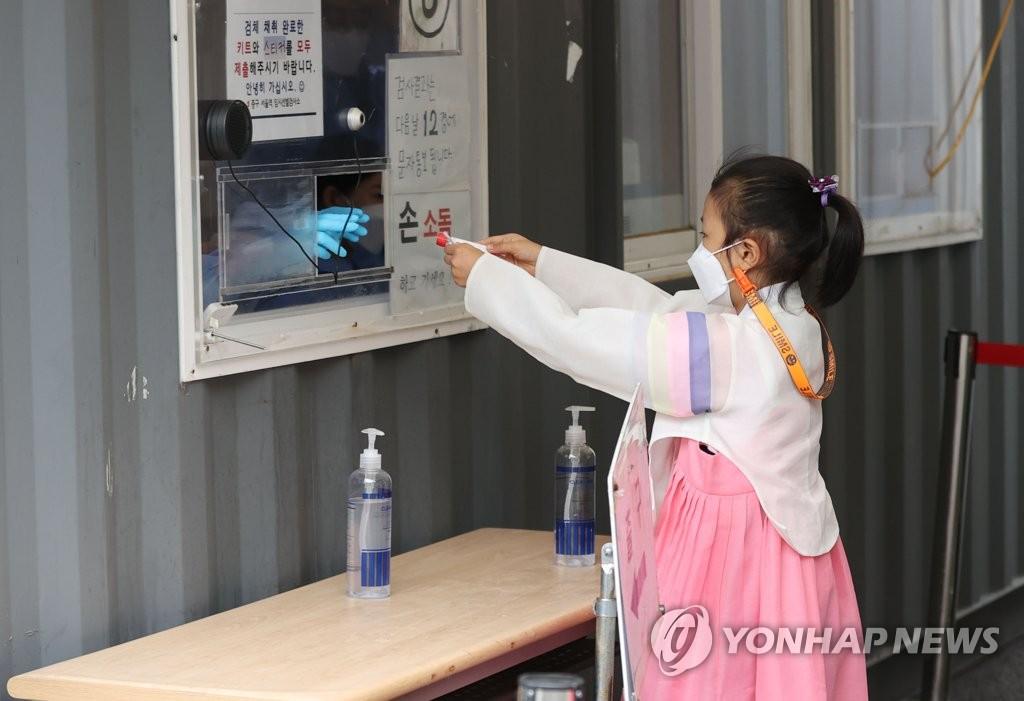 資料圖片:9月21日,在首爾火車站的臨時篩查診所,一名小朋友身穿韓服接受新冠病毒檢測。 韓聯社